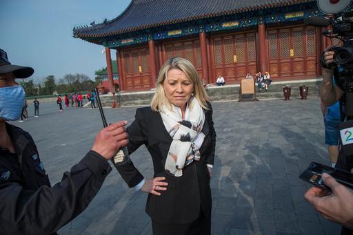 Sikkerhetsvakter prøver å stoppe pressen i å intervjue næringsminister Monica Mæland ved Himmelens tempel i Beijing torsdag.