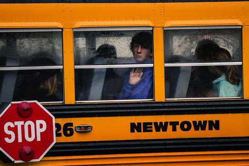 Children look out through condensation in the windows of school bus number 26 as it pulls into Newtown High School in Newtown, Connecticut