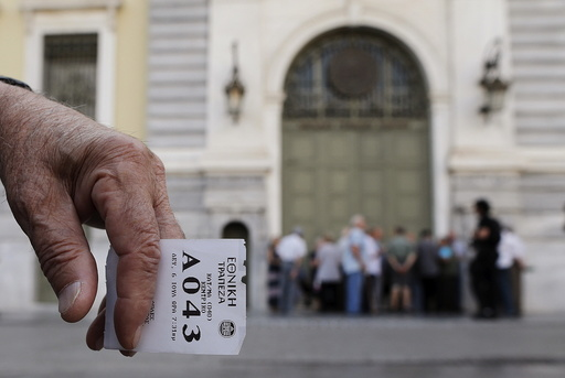 A pensioner holds his priority ticket as he waits to receive part of his pension at a National Bank branch in Athens, Greece