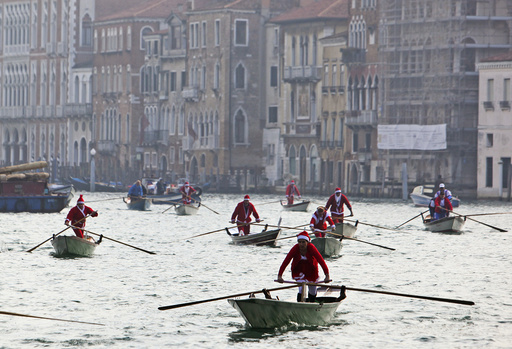 People dressed as Santa Claus ride their gondolas in the Venice lagoon