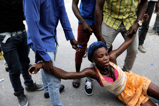 Men help a woman affected by tear gas used by National Police officers to disperse a demonstration of supporters of Fanmi Lavalas political party in the streets of Port-au-Prince, Haiti
