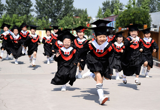 Children in gowns and mortarboards run with smiles during their kindergarten graduation ceremony in a kindergarten in Handan
