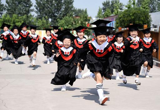 Children in gowns and mortarboards run with smiles during their kindergarten graduation ceremony in a kindergarten in Handan