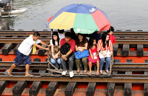 Commuters ride on a trolley along a railroad track in Manila, Philippines