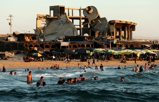 A building, that was destroyed in past Israeli shelling, is seen in the background as Palestinians swim in the Mediterranean Sea in the northern Gaza Strip