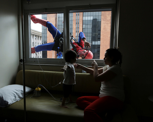 Men dressed as Spiderman jokes with patient Lucas, and his mother, looking on inside Hospital Infantil Sabara in Sao Paulo