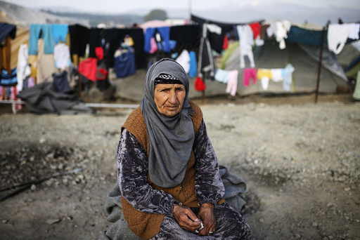 A woman sits at a makeshift camp for migrants and refugees at the Greek-Macedonian border near the village of Idomeni