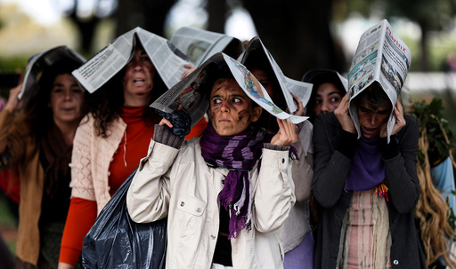 Demonstrators pretend to be ill during a theatrical performance at a protest against giant seeds company Monsanto, in Buenos Aires