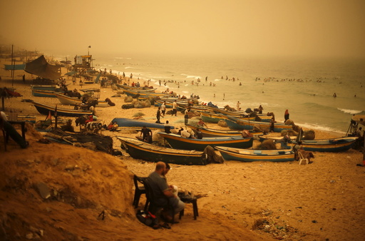 Palestinians sit on a beach along the Mediterranean Sea during a sandstorm in the northern Gaza Strip