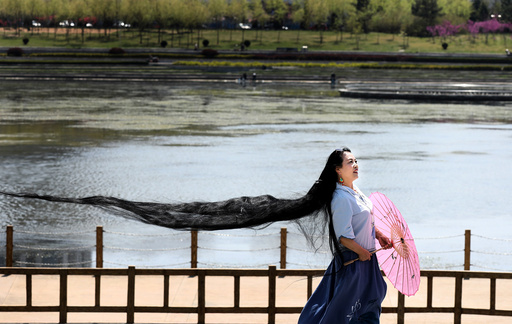 A woman with long hair poses for pictures in Weihai