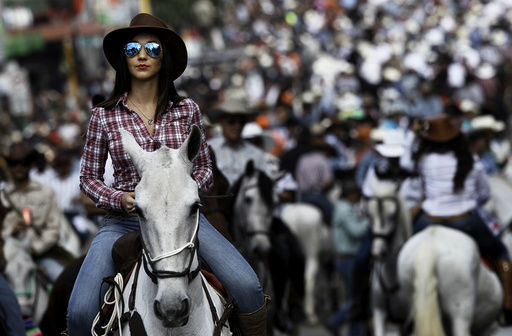 A woman takes part in a traditional horse parade through the streets of San Jose