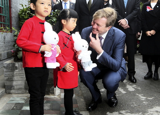 Netherlands' King Willem-Alexander gestures to a girl as he visits a hutong, or small alley, at the Qianmen area in Beijing