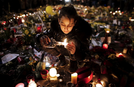 A girl lights candles as people pay tribute to the victims of Tuesday's bomb attacks, at the Place de la Bourse in Brussels, Belgium