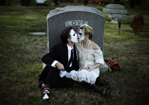 Bailey and Alexanderkiss in front of a tombstone during the 14th annual Dia de los Muertos festival at Hollywood Forever Cemetery in Los Angeles