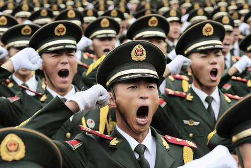 Paramilitary policemen and members of a gun salute team shout slogans at an oath-taking ceremony for the upcoming military parade to mark the 70th anniversary of the end of the World War Two, at a military base in Beijing