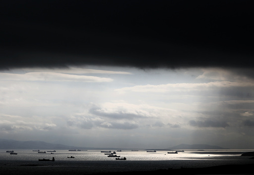 Cargo ships are seen sailing under storm clouds at open sea near the port of Piraeus, in Athens