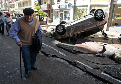 A man walks past an overturned car in the street that was damaged in flooding caused by torrential rain in Cannes