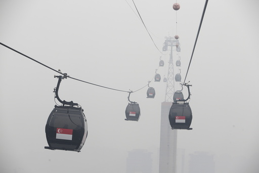 Cable cars moving towards the island resort of Sentosa are shrouded by haze in Singapore