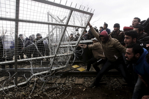 File photo of stranded refugees and migrants trying to bring down part of the border fence during a protest at the Greek-Macedonian border, near the Greek village of Idomeni