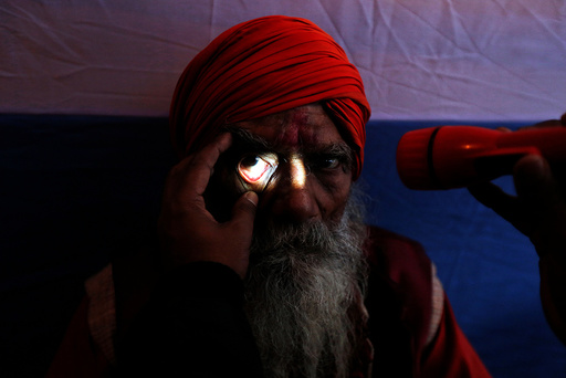 A Sadhu or a Hindu holy man undergoes an eye examination at a free eye-care camp organised by social workers at a makeshift shelter, before heading for an annual trip to Sagar Island for the one-day festival of