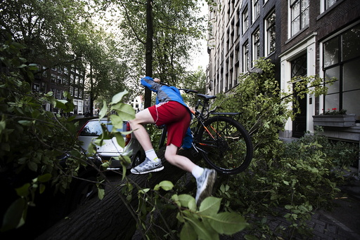 A cyclist climbs over a tree fallen atop a car after a heavy storm in Amsterdam, the Netherlands