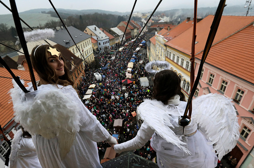 Women dressed as angels hold hands as they hang from a wire during a Christmas market in the town of Ustek
