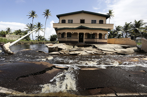 A house, badly damaged by flood water from the overflowing Nariva swamp basin following two days of rainfall in the country, sits precariously on the edge of the roadway, on the Manzanilla Mayaro Road