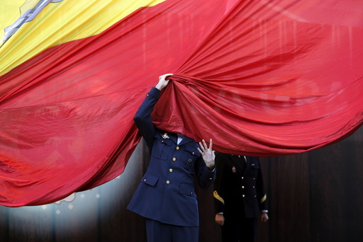 A member of the Spanish Armed Forces gets his face covered by a giant Spanish flag as he helps raise it during a ceremony to mark the 37th anniversary of the 1978 Spanish constitution in Madrid