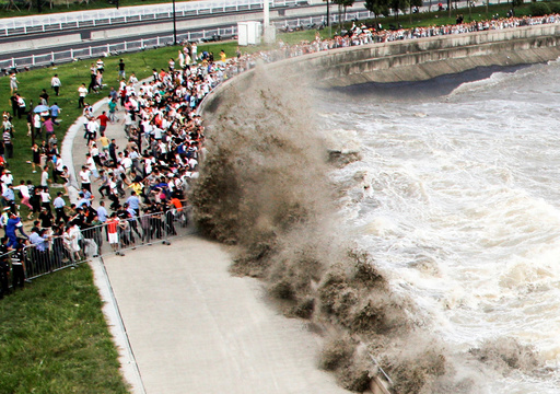 People run away from waves as they watch tidal bore in Hangzhou