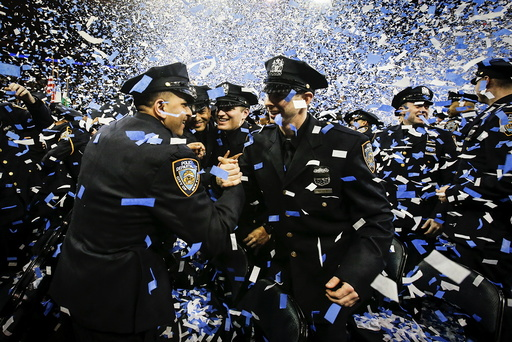 Newly inducted New York Police hug as they take part in a graduation ceremony at Madison Square Garden in the Manhattan borough of New York