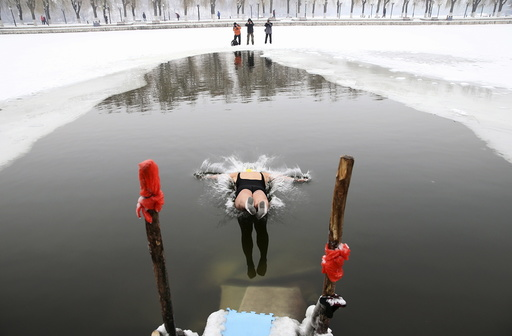 A woman dives into a partially frozen lake at a park in Shenyang