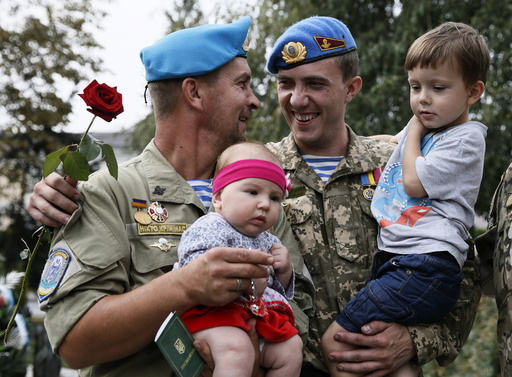 Ukrainian paratroopers, who returned from the frontline in Eastern regions, hold their children during a welcoming ceremony in Kiev