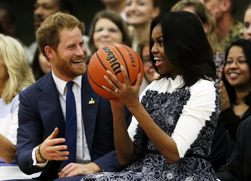 Britain's Prince Harry laughs as U.S. first lady Michelle Obama catches a basketball during a game played by wounded warriors at Fort Belvoir, Virginia