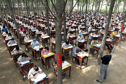 Students take term final exam among trees outside a classroom building at a middle school in Xinxiang