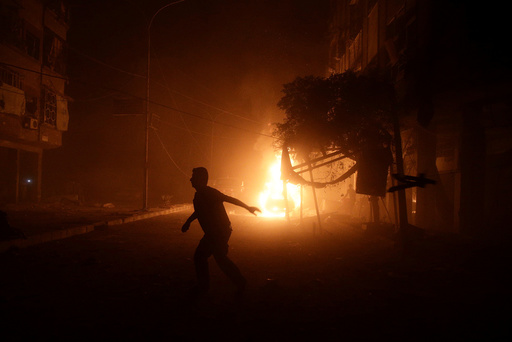 A man runs near a burning car after an airstrike in the rebel held Douma neighbourhood of Damascus