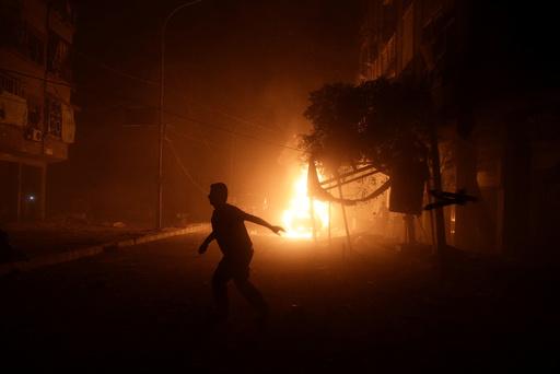 A man runs near a burning car after an airstrike in the rebel held Douma neighbourhood of Damascus