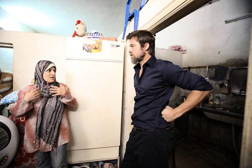 Hollywood actor Pitt, partner of UNHCR Goodwill Ambassador Jolie, listens to an Iraqi refugee living in Jaramana