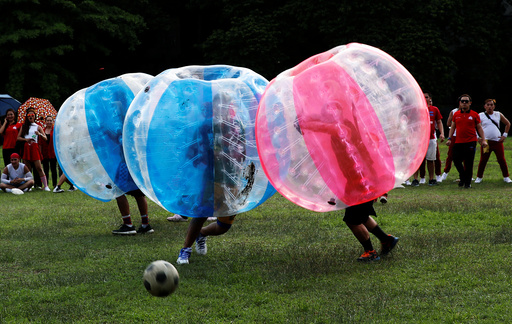 Employees of a company and their families play a friendly game of bubble bump soccer at the University of the Philippines school campus in Quezon city, Metro Manila