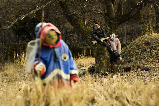 Scarecrows stand in a field in the mountain village of Nagoro