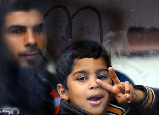 A migrant boy flashes a victory sign inside a bus at the Croatia-Slovenia border crossing at Bregana