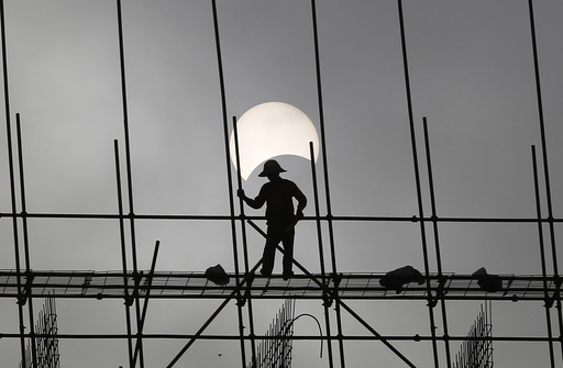 A partial solar eclipse is seen as a labourer works at a construction site in Phnom Penh, Cambodia