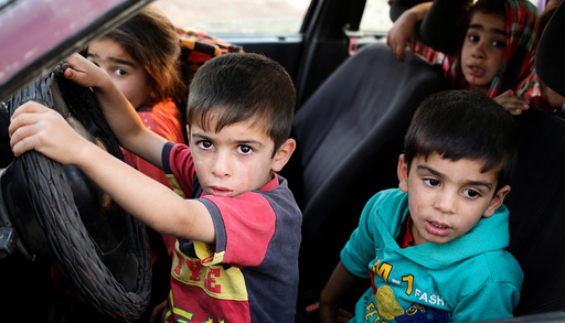 Internally displaced children sit in a car near Hassan Sham, east of Mosul