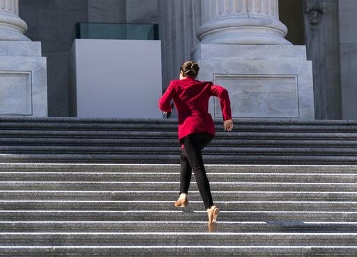 Den demokratiske kongressrepresentanten Alexandria Ocasio-Cortez spurtet onsdag opp trappene til Kongressbygningen i Washington i USA for å stemme om et nytt lovforslag som vil endre valgprosessen i USA. Foto: J. Scott Applewhite / AP / NTB