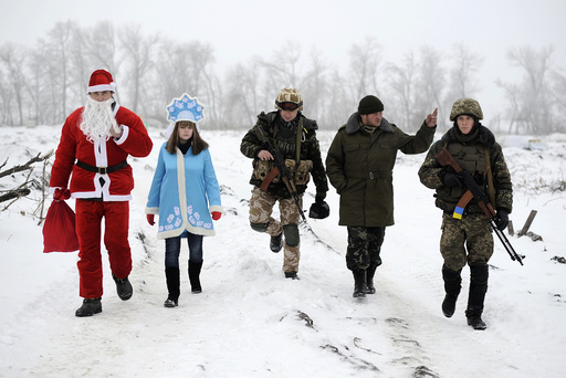 Local residents dressed as Father Frost and his granddaughter Snegurochka, walk with Ukrainian servicemen in Luhansk region
