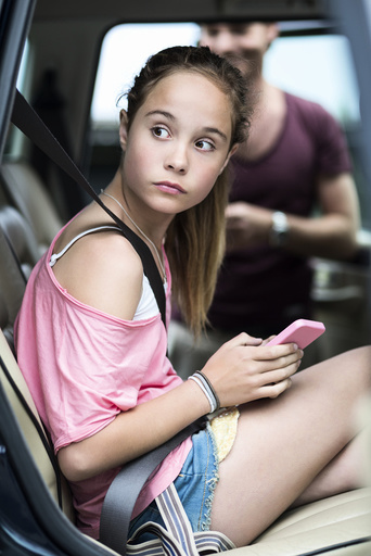Girl with mobile phone looking away while sitting in car with father in background