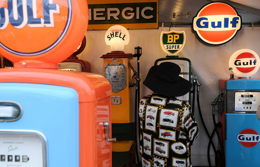 A woman views a display of old petrol pumps at the annual Goodwood Revival historic motor racing festival, celebrating a mid-twentieth century heyday of the racing circuit, near Chichester in south England