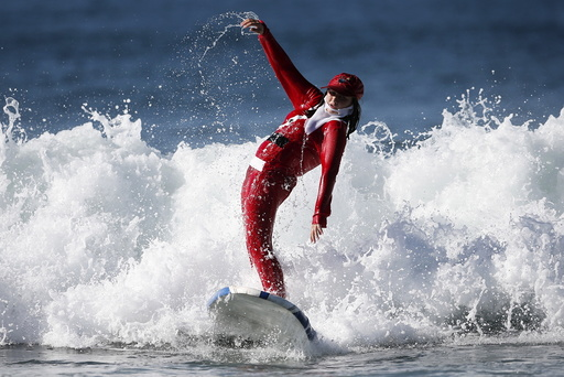A competitor surfs dressed as Santa Claus during the ZJ Boarding House Haunted Heats Halloween Surf Contest in Santa Monica