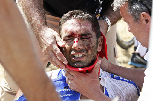 FDJ rider William Bonnet of France receives medical help as he sits on the ground after a fall during the third stage of the 102nd Tour de France cycling race from Anvers to Huy