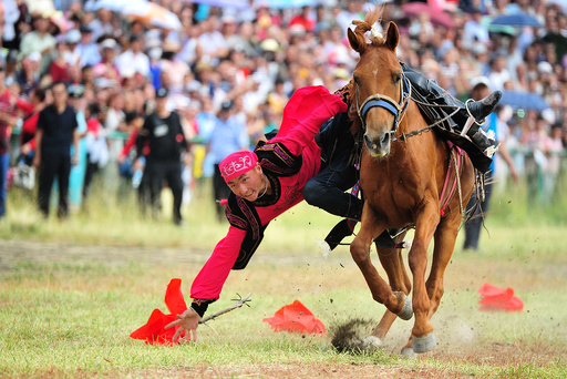 A man performs riding a horse during a traditional sports meeting in Barkol Kazakh Autonomous County