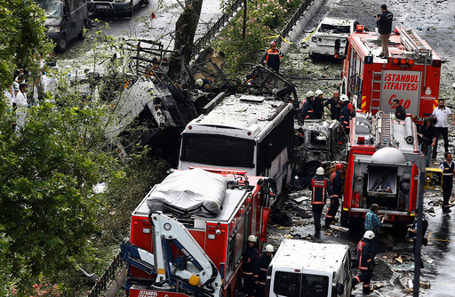 Forensic experts and firefighters stand beside a Turkish police bus which was targeted in a bomb attack in Istanbul